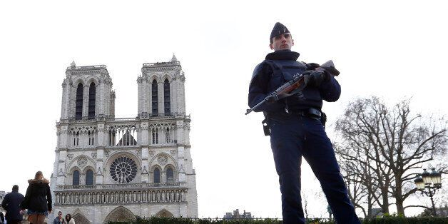 FILE - In this March 27, 2016 file photo, a French Police officer stands guards as worshipers arrive...