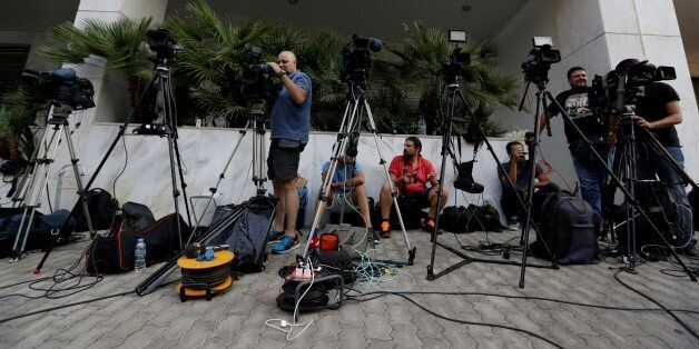 TV crews work outside the Greek Secretariat General for Media and Communication in Athens on Wednesday,...