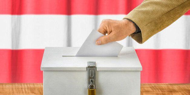 Man putting a ballot into a voting box -