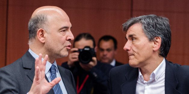 EU Commissioner for Economic and Financial Affairs, Taxation and Customs Pierre Moscovici, left, talks...
