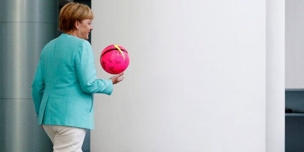 German Chancellor Angela Merkel holds a ball given by international female soccer players of