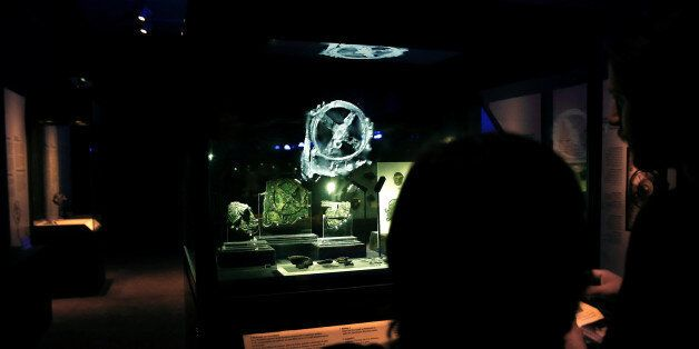 Visitors look at the displayed fragments of the ancient Antikythera Mechanism at the National Archaeological...