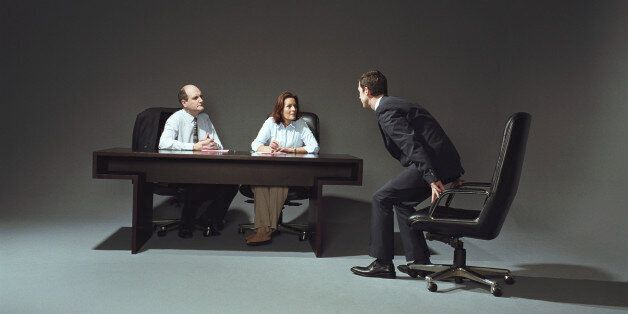 Young businessman being interviewed by two