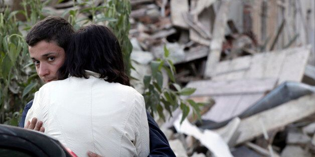 Two people hug each other next to the remains of a collapsed house following an earthquake in Pescara...