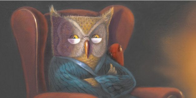An owl with glasses in a robe with arms crossed in an armchair
