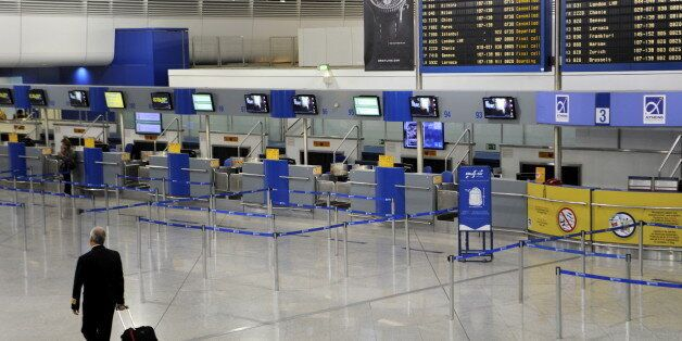 A man makes his way through the empty check-in area of the Athens Eleftherios Venizelos International...