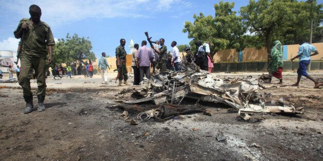 A Somali policeman walks past the wreckage of a car destroyed during an explosion outside the headquarters...