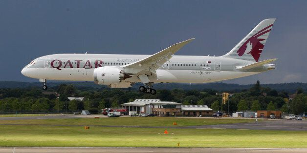 FILE- in this file photo dated Wednesday, July 11, 2012, onlookers watch as a Qatar Airways Boeing 787...