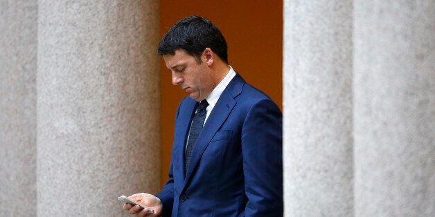 Italy's Prime Minister Matteo Renzi checks his phone as he waits for the arrival of leaders for a meeting,...