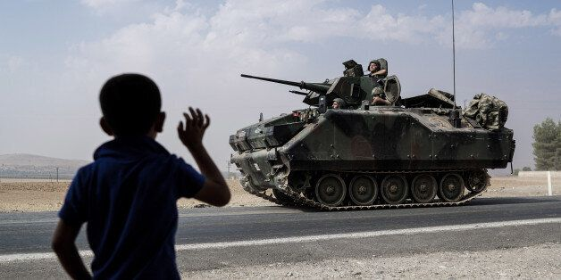 A child waves toward Turkish troops heading to the Syrian border, in Karkamis, Turkey, Friday, Aug. 26,...