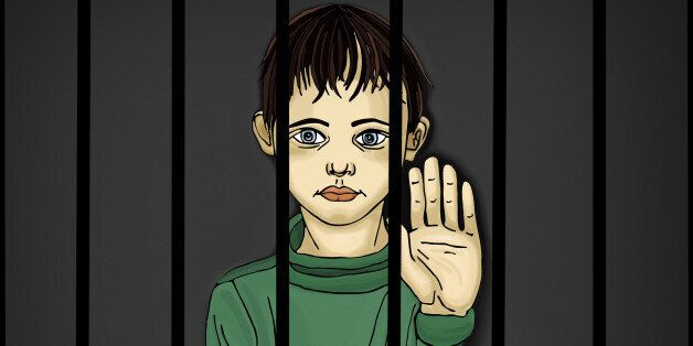 The child in prison. Children of criminals. Behind bars. Juvenile criminals. Angry and unhappy boy showing...