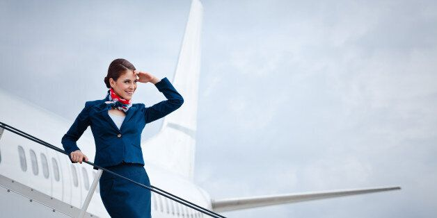 'Outdoor portrait of a beautiful flight attendant standing on the aircraft stairs, waiting for travellers.'