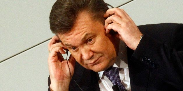 Ukrainian President Viktor Yanukovych adjusts his earphones during the 48th Conference on Security Policy...
