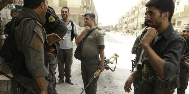 Members of the Kurdish police known as the Asayesh and the Kurdish People's Protection Units(YPG) gather...