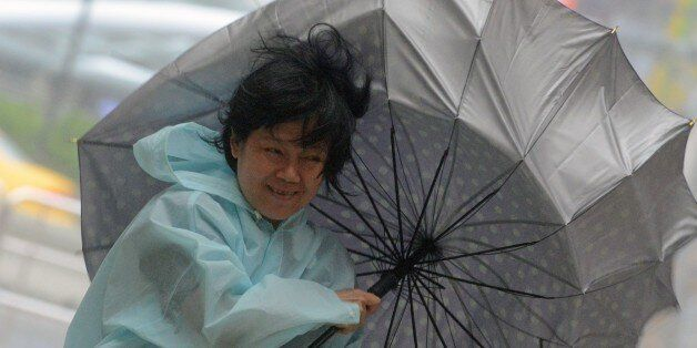 A woman uses an umbrella against strong wind and rain brought by typhoon Dujuan at Tamshui district,...