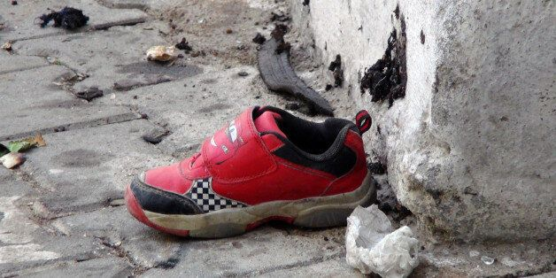 The shoe of a young victim and a piece of metal lay near the scene just hours after Saturday's bomb attack...