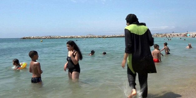 FILE - In this Aug.4 2016 file photo made from video, Nissrine Samali, 20, gets into the sea wearing...