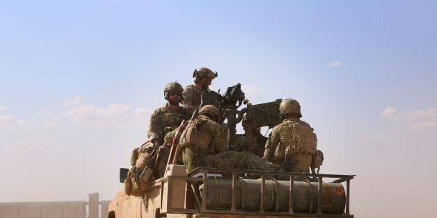 Armed men in uniform identified by Syrian Democratic forces as US special operations forces ride in the...