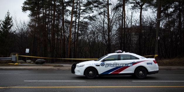 TORONTO, ON - March 14 - A police car drives past police tape around the park near Don River Trail at...