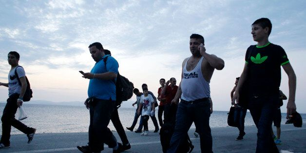 Syrians migrants head to Mytilene to be counted by Greek authorities after they arrived with an overcrowded...