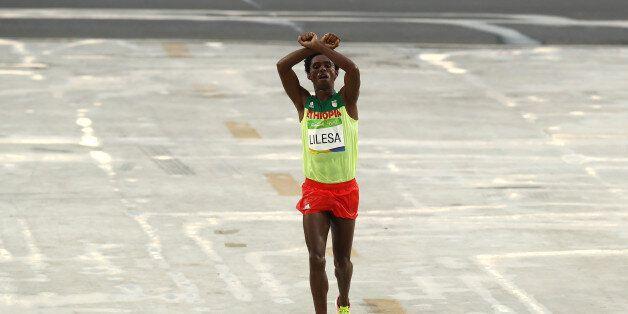 RIO DE JANEIRO, BRAZIL - AUGUST 21: Feyisa Lilesa of Ethiopia celebrates as he crosses the line to win...