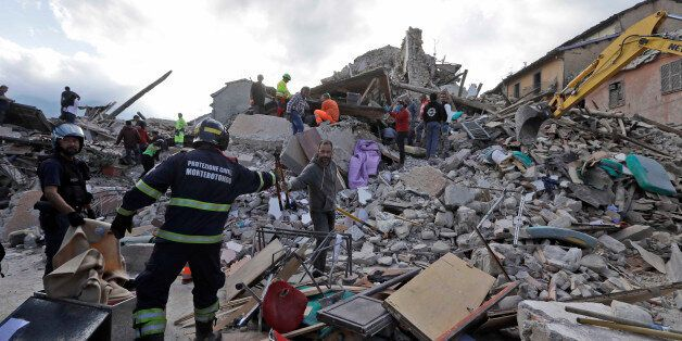 Rescuers search for survivors through the rubble of collapsed buildings following an earthquake, in Amatrice,...
