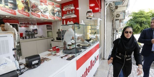 An Iranian worker prepares a crepe at Nutella Bar, a popular chain selling waffles and crepes in Tehran...