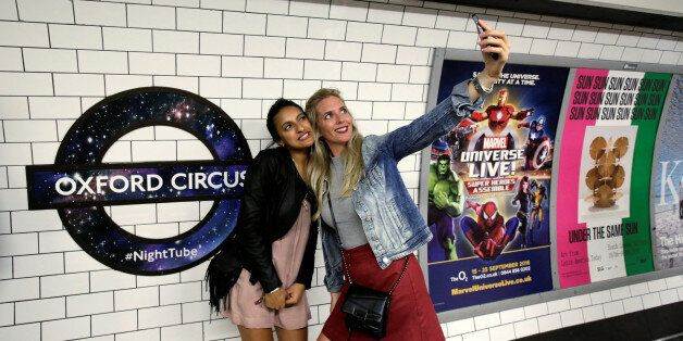 Passengers pose for a selfie as they wait for the Night Tube train service at Oxford Circus on the London...