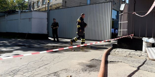 Firefighters work at the site of a fire in a Moscow warehouse on August 27, 2016.At least 16 migrant...