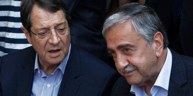 Cyprus President Nicos Anastasiades, left, and Turkish Cypriot leader Mustafa Akinci, speak as they sit...