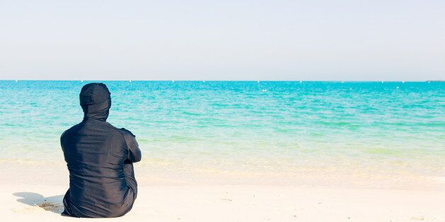 young woman wearing burkini sitting by the beach in