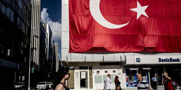 Pedestrians pass a giant Turkish national flag hanging above a DenizBank AS bank branch in Istanbul,...