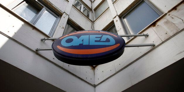 A logo sits on display outside an OAED employment center in Athens, Greece, on Friday, May 8, 2015. Prime...