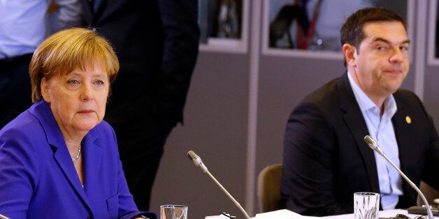 German Chancellor Angela Merkel, left, and Greek Prime Minister Alexis Tsipras attend a round table meeting...