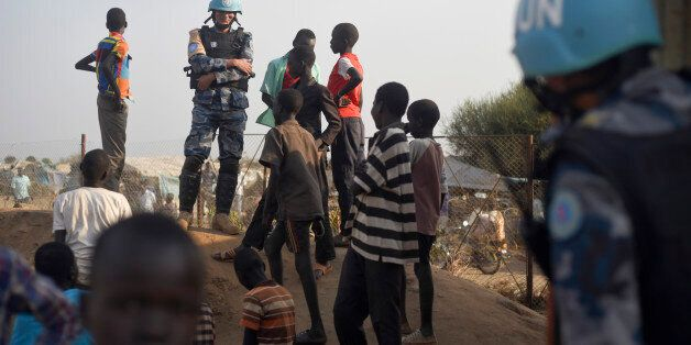 In this photo taken Tuesday, Jan. 19, 2016, a United Nations peacekeeper stands with displaced children...