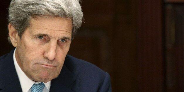 U.S. Secretary of State John Kerry listens as Iran's Foreign Minister Mohammad Javad Zarif (unseen) speaks...