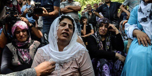 TOPSHOT - Women cry during a funeral for a victim of last night's attack on a wedding party that left...