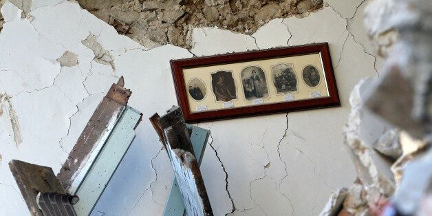 The interior of an house with old pictures still hanging on a wall is seen in Amatrice, following an...