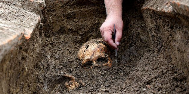 An archaeologist works over an uncovered skeleton at the Viminacium site, around 100km east from Belgrade,...