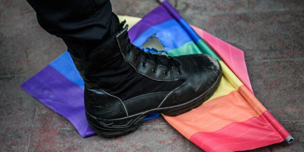 TOPSHOT - A Turkish anti-riot police officer steps on a rainbow flag during a rally staged by the LGBT...