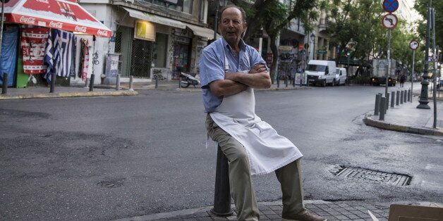 A street vendor waits for customers during early morning in Athens, Greece, July 4, 2015. If a 'No' in...