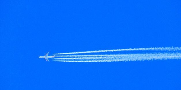 Airplane with chemtrails on blue sky