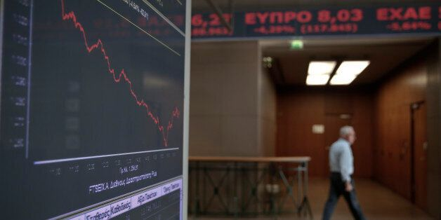 An employee walks past a screen showing a tumbling index at the Athens Stock Exchange on Wednesday Oct....
