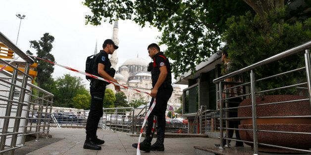 Police secures the area near the site where a Turkish police bus was targeted in a bomb attack in a central...
