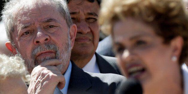 Brazil's former President Luiz Inacio Lula da Silva listens as suspended President Dilma Rousseff addresses...