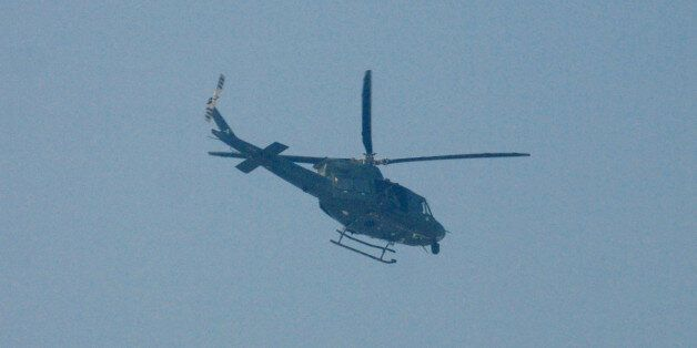 An army helicopter flies over the Army Public School that in under attack by Taliban gunmen in Peshawar,...