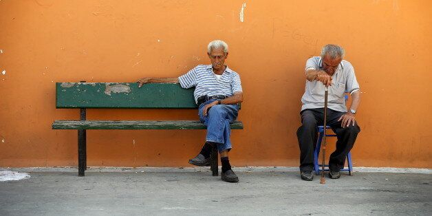 Two men sit on a bench in the village of Meyisti on the Island of Kastellorizo, Greece, July 4, 2015....