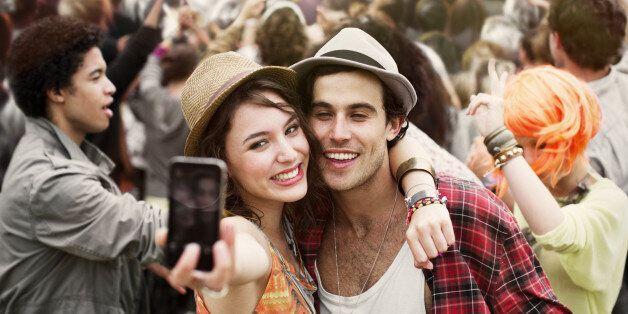 Couple taking self-portrait at music festival