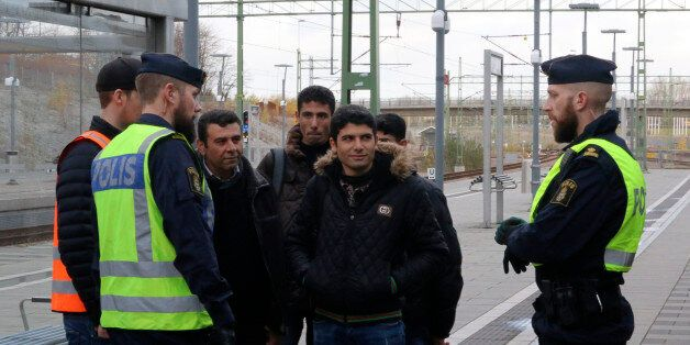 Swedish police officers speak to a group of people at the Hyllie train station near Malmo, Sweden, November...