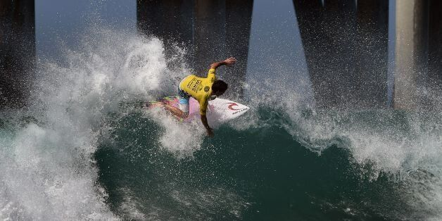 Mason Ho of Hawaii surfs beside the pier in his men's heat during the first round of the US Open of Surfing...